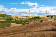Row Of Wind Turbines In A Wind Farm On The Hilltops Viewed Across Rolling Agricultural Land
