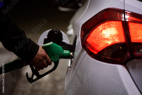 Fototapeta Gas station worker in workwear refueling luxury car with gasoline holding filling gun at the station. obraz