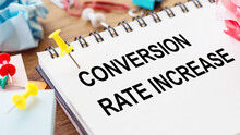 CONVERSION RATE INCREASE - Text On A Notepad With Wrinkled Paper And Paper Needles On Wooden Background.