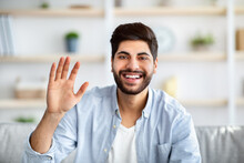 Greeting Gesture Concept. Happy Arab Man Waving Hand To Camera, Saying Hello And Laughing