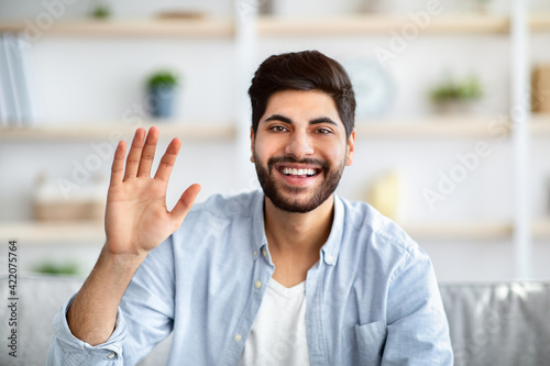 Fototapeta Greeting gesture concept. Happy arab man waving hand to camera, saying hello and laughing obraz