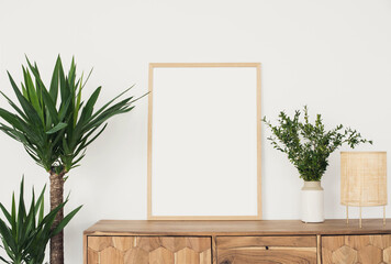 Blank picture frame mockup on white wall. White living room design. View of modern scandinavian style interior with flowers. Home staging and minimalism concept. Artwork poster showcase