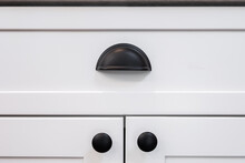 Photograph Of A Matte Black Drawer Cup Pull Handle On A White Cabinet.
