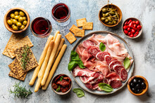 Appetizers With Differents Antipasti, Charcuterie, Snacks And Red Wine. Sausage, Ham, Tapas, Olives And Crackers For Buffet Party. Top View, Flat Lay