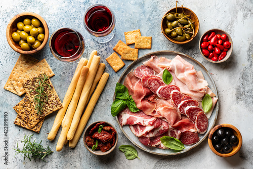 Fototapeta Appetizers with differents antipasti, charcuterie, snacks and red wine