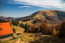 Mountain Cottage In The Autumn Mountains With Flying Leafes In The Sky
