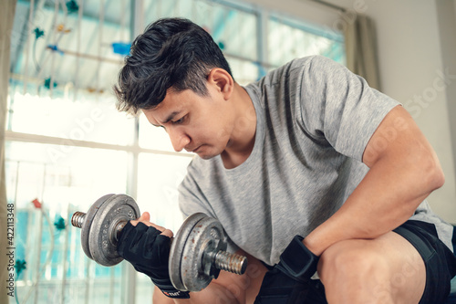 Young man doing exercises biceps with dumbbell on yoga mat in living room at home Fototapet