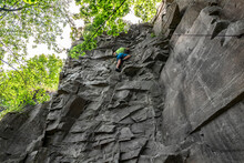 Man Climber With Climbing Gear Equipment Climbs On Rock Wall. Canyon Rocks In Green Forest
