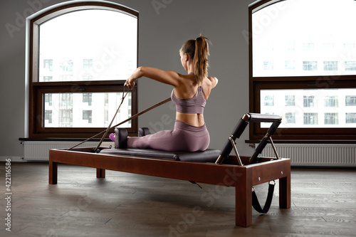 Young girl doing pilates exercises with a reformer bed Fototapete