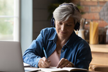 Diligent Aged Student. Focused Elderly Hispanic Woman In Headphones Watch Webinar On Laptop Screen Take Notes To Paper Notebook. Mature Old Lady In Headset Study Online Take Part At Education Training