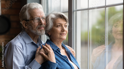 Obraz Looking in future. Loving senior man husband embrace aged wife from behind support encourage share feeling of beloved woman. Elderly spouses hug look at window meet twilight years together. Copy space - fototapety do salonu