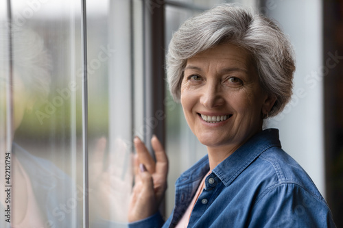 Portrait of happy beautiful aged 50s female of hispanic ethnicity stand by large window look at camera. Head shot of attractive healthy senior latin woman enjoy active life in retirement. Copy space