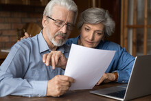 Every Paper Needs Attention. Interested Old Age Married Couple Do Paperwork Engaged In Reading Document. Focused Retired Spouses Study Terms Conditions Of Insurance Policy Think On Signing Agreement