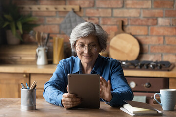 Modern day pensioner. Smiling mature latina woman sit at home office by kitchen table watch video on tab computer screen. Old age grandmother enjoy reading e book on tablet pc scroll news on websites