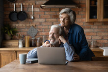 Looking Forward Together. Loving Aged Spouses Pensioners Spend Time Together At Country Cottage Kitchen Use Laptop Dreaming. Bonding Senior Couple Husband Wife Hug Look At Distance Imagine Good Future