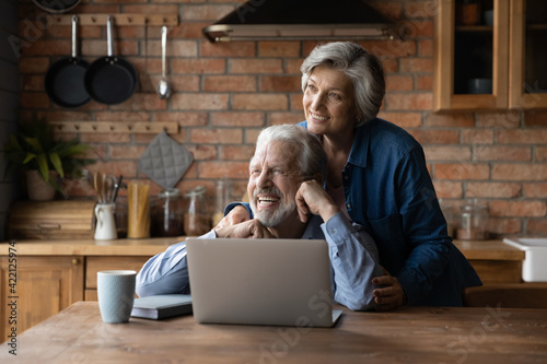 Obraz Looking forward together. Loving aged spouses pensioners spend time together at country cottage kitchen use laptop dreaming. Bonding senior couple husband wife hug look at distance imagine good future - fototapety do salonu