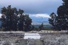 Paso De Madera En La Vieja Vía Del Tren En La Estación De Gascones-Buitrago Con Unos Copos De Nieve. Paisaje Rural Tras La Primera Nevada Otoñal En Esta Estación Olvidada De La Comunidad De Madrid, Es