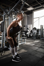 Vertical Full Length Shot Of A Young Sportswoman Exercising In Crossover Gym Machine