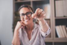 Focus On Bunch Of Keys From House Flat Apartment In Hand Of Smiling Female. Blurred Portrait Of Confident Woman Professional Realtor Offering New Dwelling Real Estate Unit To Potential Buyer. Close Up