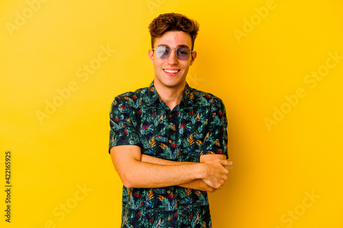 Young caucasian man wearing a Hawaiian shirt isolated on yellow background who feels confident, crossing arms with determination.