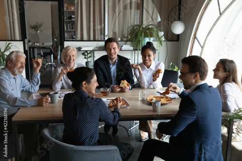 Papel de parede Smiling diverse employees sit in office have fun enjoy pizza on work lunch break together