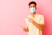 Young Caucasian Man Wearing A Protection For Coronavirus Isolated On Pink Background Excited Pointing With Forefingers Away.