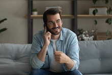 Close Up Smiling Man Wearing Glasses Talking On Phone, Sitting On Cozy Couch At Home, Happy Young Male Enjoying Pleasant Conversation With Friend, Holding Smartphone, Ordering Food Or Chatting