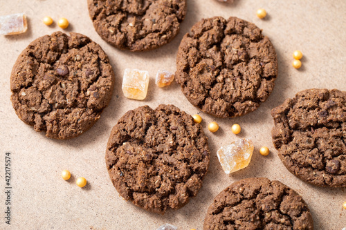 Photo Chocolate granola cookies with brown cane sugar, spread out on a beige cardboard background