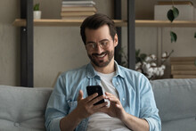 Close Up Smiling Man Wearing Glasses Using Smartphone, Sitting On Couch At Home, Happy Young Male Looking At Phone Screen, Browsing Apps, Chatting Or Shopping Online, Having Fun With Gadget