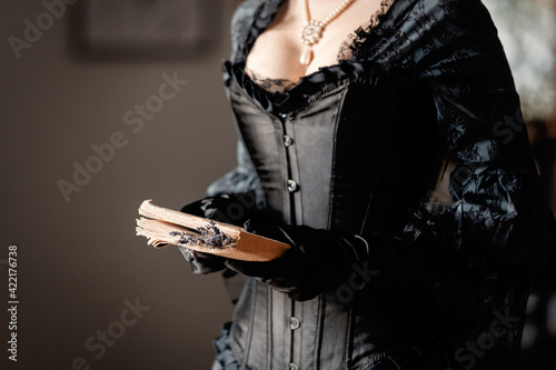 Fototapeta Beautiful woman in black dress holding a book and lavender flowers indoor obraz