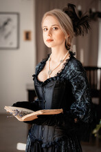 Beautiful Woman In Black Dress Holding A Book And Lavender Flowers Indoor