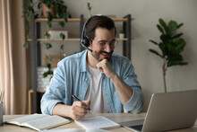 Close Up Smiling Man Wearing Headphones And Glasses Involved In Online Lesson, Looking At Laptop Screen, Writing Taking Notes, Happy Motivated Student Watching Webinar, Studying At Home