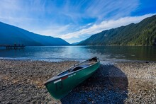 Green Canoe Left On A Rocky Beach With A Glacier Lake And Mountains In The Background At Lake Crescent, Washington In Olympic National Park