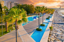 Sunset In Cyprus. Sun Sets In Limassol. Limassol In A Summer Fan. Evening Panorama Cyprus. Bird Eye View Of Mediterranean Landscape. Travel In Cyprus. Palm Trees On Limassol Waterfront