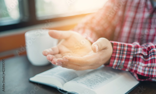 Foto Christian hand while praying and worship for christian religion with blurred of her body background, Casual man praying with her hands together over a closed Bible