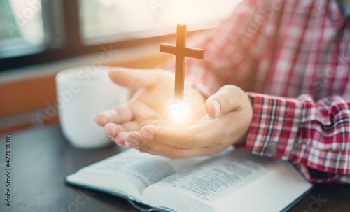 Christian hand while praying and worship for christian religion with blurred of her body background, Casual man praying with her hands together over a closed Bible Fotobehang