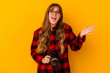 Young Photographer Caucasian Woman Isolated On Yellow Background Receiving A Pleasant Surprise, Excited And Raising Hands.