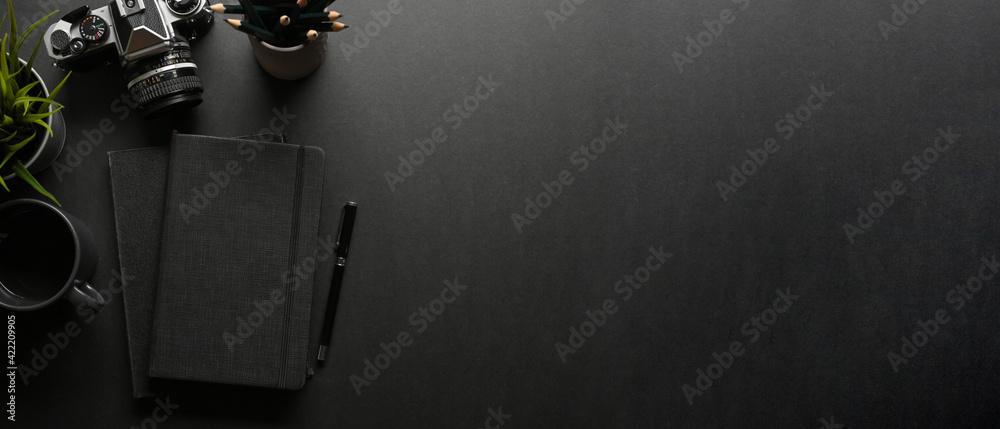 Fototapeta Dark creative workspace with notebook, pen, camera and copy space, creative mock up scene