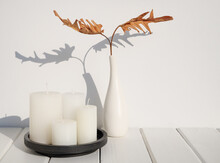 Spa Composition With White Candles And Philodendron Dry Leaf In Modern Ceramic White Vase On Wooden Table Earth Tone Room Interior ,long Shadow