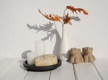Stone Podium And Spa Composition With White Candles ,elephant Statue And Philodendron Dry Leaf In Modern Ceramic White Vase  On Wooden Table Earth Tone Interior,long Shadow