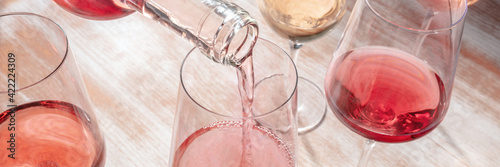 Fototapeta Pouring rose wine panorama with various wineglasses obraz