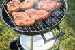 canvas print picture - Marinierte Schweine Fleisch Nackensteaks roh grillen mit Rauch auf Holzkohle Kugelgrill im Garten an Sommer Abend