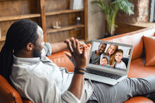 African American Man With Dreadlocks Using App For Online Video Communication With Family, Friends, Looking And Waving At Laptop Desktop With A Group Of Happy People, Staying Connected In Pandemic