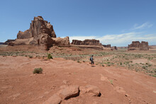A Hiker Looking At The Vast Landscape And Red Sandstone Formations At Arches National Park In Utah On A Sunny Day