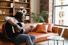Concentrated Young African American Guy Learning How To Play Guitar, Watching Online Tutorial Virtual Class Via Laptop At Home During Coronavirus, Sitting On The Sofa, Recording Song Streaming Music