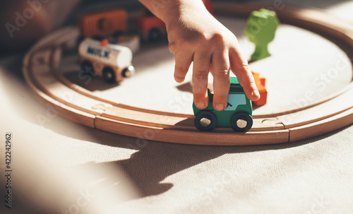Fotografía caucasian kid is playing with toy train on the railway on the floor