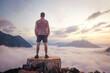 Leinwandbild Motiv Man standing on a mountain top above the clouds