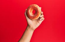 Hand Of Hispanic Man Holding Donut Over Isolated Red Background.