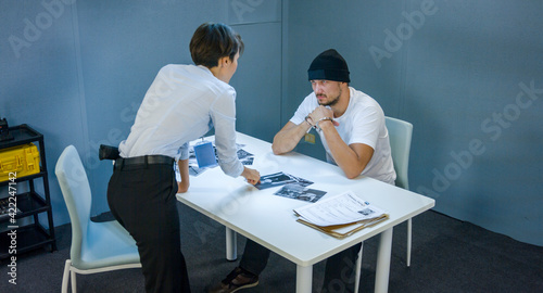 Fotografia Woman detective shows pictures of suspected criminals and robber