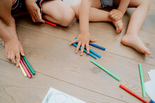 Siblings Drawing With Colored Markers While Lying On Wooden Floror At Home In The Living Room. Arts And Crafts For Kids. Paint On Children Hands. Creative Little Artist At Work.